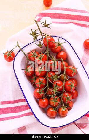 Cherry tomatoes in an enamel dish - Stock Photo