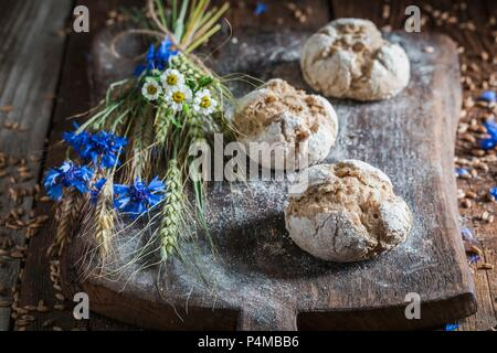 Healthy wholemeal bread rolls with ears of corn and field flowers on a wooden board - Stock Photo