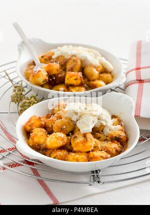 Gratinated gnocchi with ricotta and Pecorino cheese - Stock Photo
