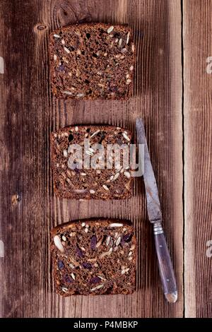 Three slices of banana bread with sunflower seeds, pumpkin seeds, cranberries, apple butter and walnut flour - Stock Photo
