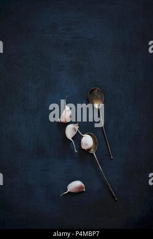 Garlic cloves and vintage silver spoons on a black background - Stock Photo
