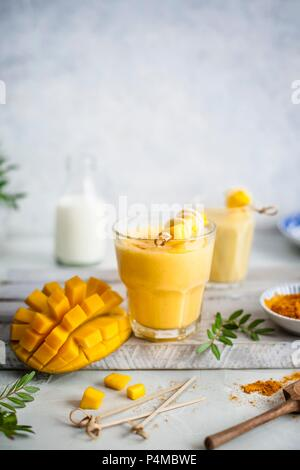 Mango lassi with turmeric and honey, fresh mango on a side - Stock Photo