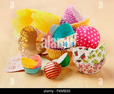 Various types and colours of cupcake and muffin cases on a wooden surface - Stock Photo