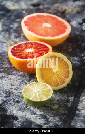 Assorted citrus fruit, halved - Stock Photo