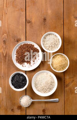 Various types of rice in bowls on wooden surface - Stock Photo