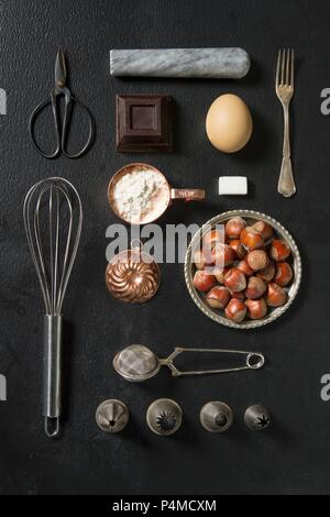 An arrangement of kitchen utensils and baking ingredients on a dark surface - Stock Photo