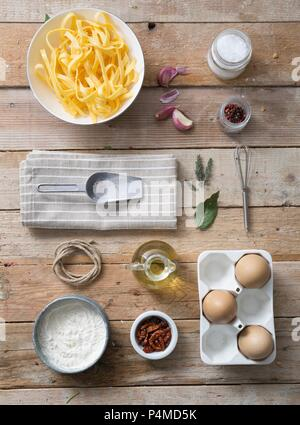 Fresh tagliatelle with ingredients on a wooden surface - Stock Photo