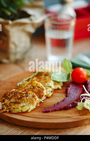 Potato and vegetable fritters on a wooden chopping board - Stock Photo