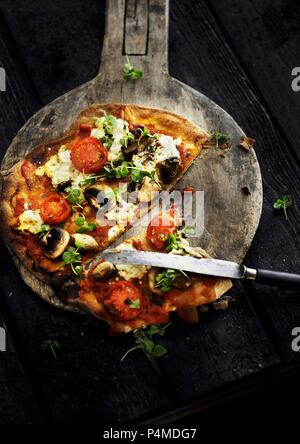 A sliced vegetarian pizza on a wooden pizza paddle - Stock Photo