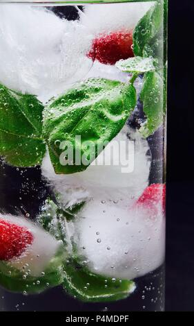 Ice cubes with raspberries and basil in a glass of water - Stock Photo