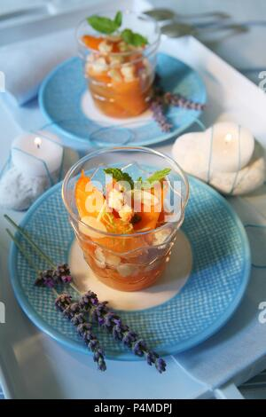 Vin Santo peaches with roasted flaked almonds, biscuit and mint leaves - Stock Photo