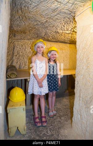 Child / children / kid / kids / family enjoy exploring the air raid shelter tunnel / tunnels inside / underground at the Malta At War Museum, Malta. - Stock Photo