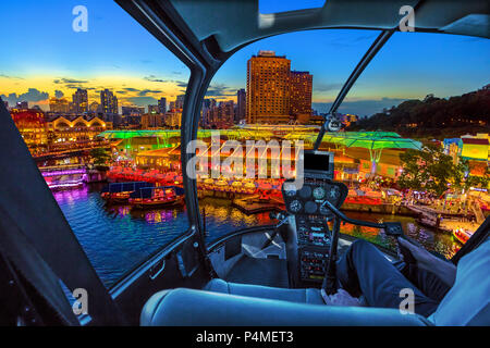 Helicopter cockpit interior flying on aerial skyline of Clarke Quay and riverside area at sunset in Singapore, Southeast Asia. Waterfront skyline on Singapore River. Popular nightlife attraction. - Stock Photo