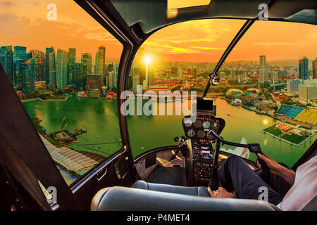 Helicopter cockpit interior flying on Singapore marina bay panorama of financial district skyscrapers at sunset on the harbor skyline. Aerial Singapore cityscape at twilight time. - Stock Photo