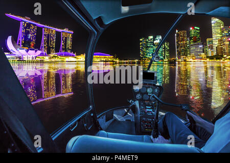Helicopter cockpit interior flying on Panorama of Singapore buildings and skyscrapers of downtown reflected in the sea. Singapore skyline by night flight and nocturnal scene of marina bay waterfront - Stock Photo