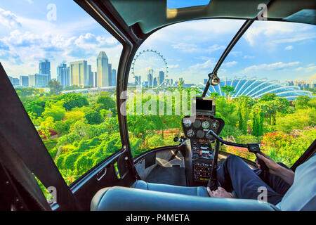 Helicopter cockpit interior flying on aerial view of Singapore cityscape and garden park by the bay. Famous marina bay promenade of Singapore. - Stock Photo