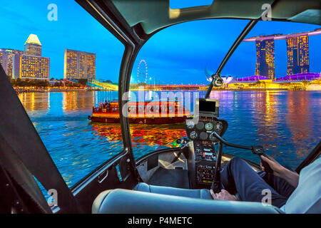 Helicopter cockpit interior flying on Singapore buildings panorama over skyscrapers and ferris wheel reflected in the sea. Tourist cruise boat sails in evening bay. Singapore waterfront dusk skyline. - Stock Photo