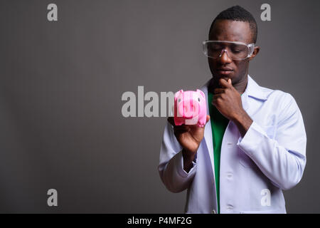 Young African man doctor wearing protective glasses against gray