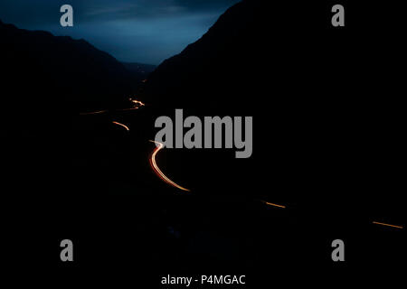 Cars trail lights on the Llanberis Pass at dusk, Snowdonia, Gwynedd, Wales, UK - Stock Photo