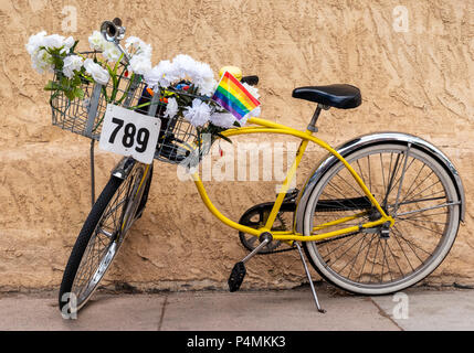Colorful yellow commuter bicycle with artificial flowers in the front basket; Salida; Colorado; USA - Stock Photo