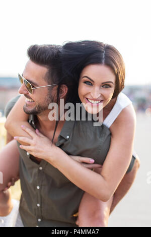 Stylish man carrying girlfriend on back outdoors, couple in fun and happiness - Stock Photo