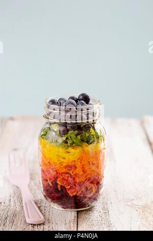 Rainbow salad in a glass with beetroot, carrots, yellow peppers, lettuce and blueberries - Stock Photo