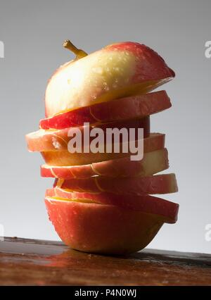 An apple cut into slices, with water drops - Stock Photo