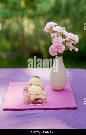 Strawberry crumble with vanilla ice cream in dessert dishes on a garden table - Stock Photo