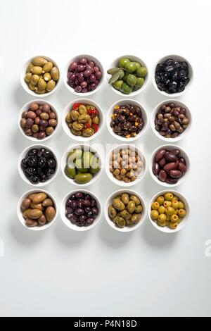 Various prepared olives in white bowls - Stock Photo
