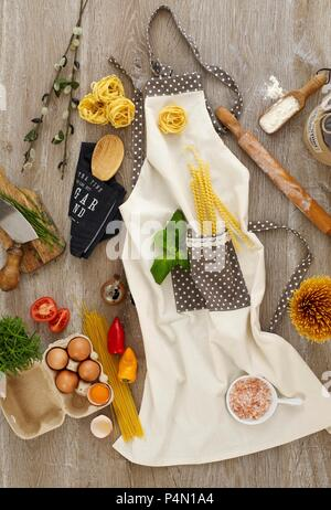 Ingredients and cooking utensils for pasta dishes on an apron - Stock Photo