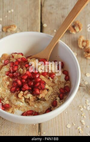 Vegan coconut yoghurt with oats, walnuts, pomegranate seeds and agave syrup - Stock Photo
