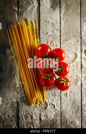 Cherry tomatoes with spaghetti and flour on a wooden table - Stock Photo