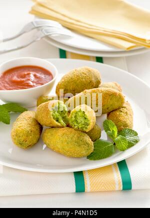 Pea croquettes with a tomato dip - Stock Photo