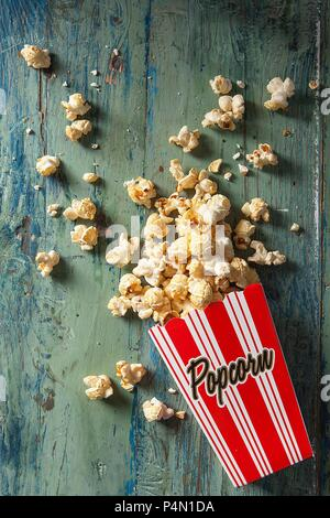 Boxed popcorn spilling out onto an aqua wooden board - Stock Photo