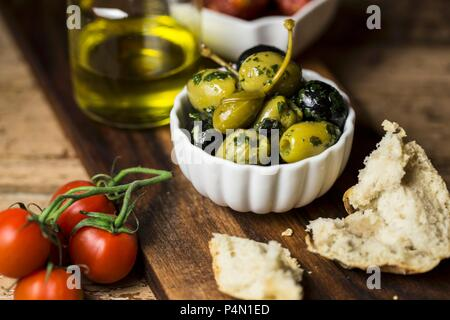 Herb olives, caper fruits, tomatoes and bread - Stock Photo