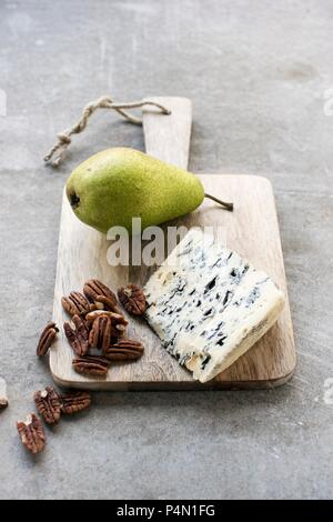 Roquefort, pecan nuts and a fresh pear on a wooden board - Stock Photo