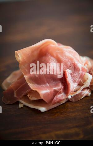 A pile of Parma ham slices on a wooden board - Stock Photo