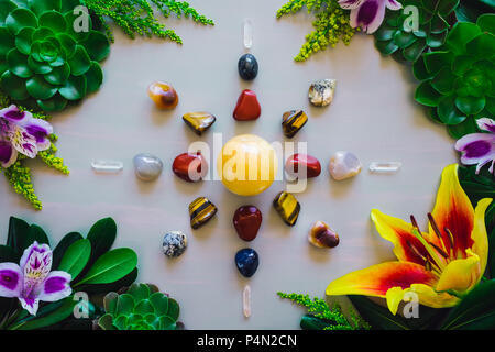 Crystal Grid on Grey Table with Red Jasper, Mixed Agate, Quartz, Tiger's Eye and Aventurine with Summer Botanicals - Stock Photo