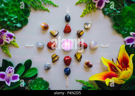 Crystal Grid with Candle Center and Red Jasper, Mixed Agate, Quartz, Tiger's Eye and Aventurine on Grey Table with Summer Botanicals - Stock Photo
