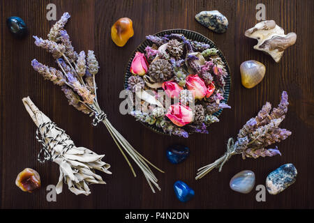 Dried Lavender, Rose and Sage with Agate, Fire Agate, Dendridic Agate and Snakeskin Agate on Dark Wood Table - Stock Photo