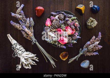 Dried Lavender, Rose and Sage with Red Jasper, Agate, Tiger's Eye and Pyrite on Dark Wood Table - Stock Photo