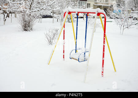 Children's swing, covered with a thick layer of snow after a heavy snowfall . - Stock Photo