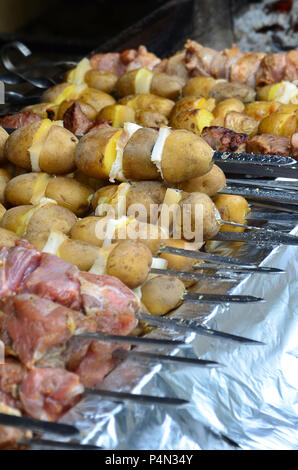 Raw meat and potatoes are planted on metal skewers. The process of cooking shish kebabs. Russian and Ukrainian camp food - Stock Photo