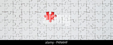 The texture of a white jigsaw puzzle in an assembled state with one missing element forming a red space . - Stock Photo
