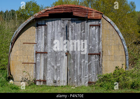 Dilapidated wooden front doors of Nissen Hut with rusted corrugated iron roof, with bushes growing around the edges.