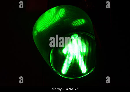 Night photo of a traffic light for pedestrians, which lights up in green . - Stock Photo