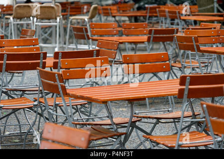 Unoccupied chairs and tables in a garden restaurant with table legs and chair legs made of iron and wooden tops, Germany - Stock Photo