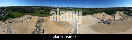 Large construction site with the sand planum for a new development and a rain retention basin in the background, panoramic view from the air, Germany - Stock Photo