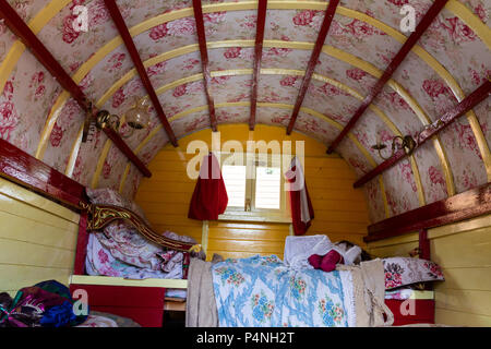 Inside a gypsy caravan showing the floral paintwork and colourful decoration. - Stock Photo