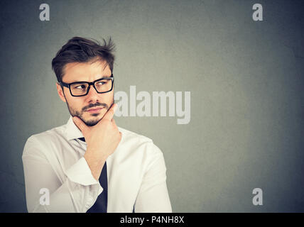 Young bearded man in contemplation looking up and planning new business strategy and creating idea on gray background - Stock Photo